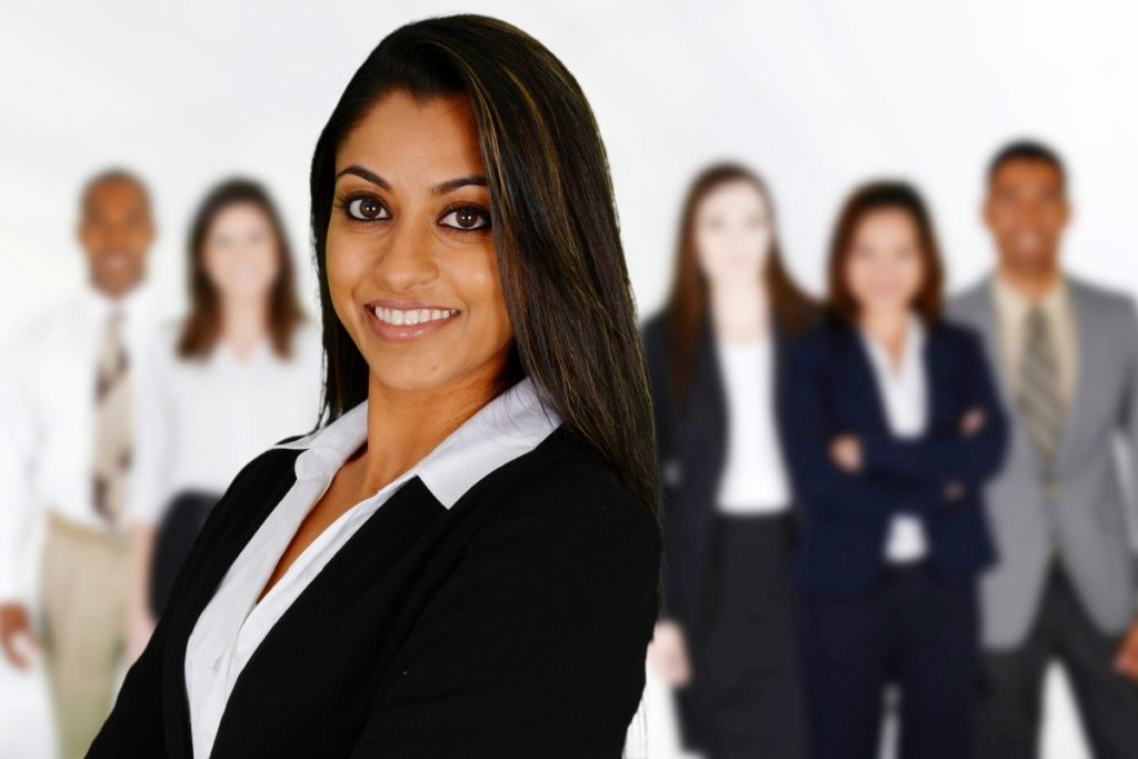 Woman in business suit in front of blurred out people.