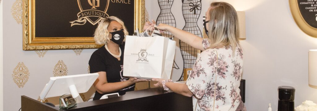 Woman shopping at Tonyan Grace boutique wearing a face mask.